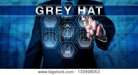 Security software developer pushing GREY HAT on a virtual control screen. British English spelling. Computer security metaphor for a cracker hacking to expose and offer to fix a security flaw.
