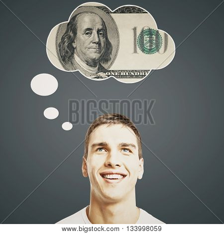 Handsome young man thinking about money on dark grey background