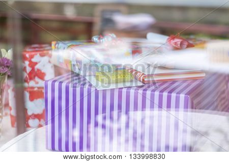 A table with gifts and birthday presents behind a windowpane wirh refelctions  in the glass