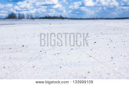 Landscape in the field of quartz white sand with a remote horizon and cloudy sky out of focus.