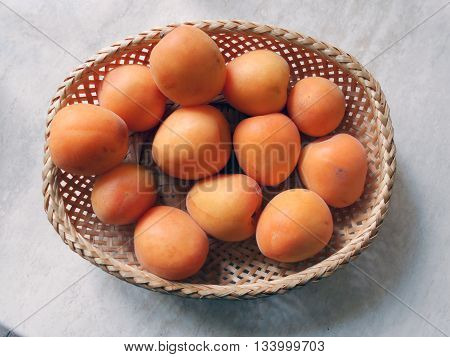 Apricots are in a wicker basket. Fruits ripe with a velvety skin.