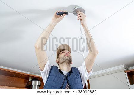 A male electrician fixing light on the ceiling with screwdriver. Close-up.