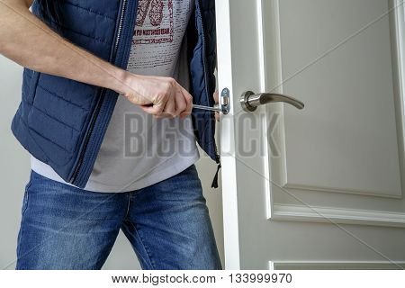 Man carpenter fixing lock in door with screwdriver at home. White door. Close-up.