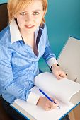 Businesswoman With Pencil Checks The Documents In A Folder
