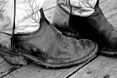 pic of buckaroo  - muddy cowboy boots in black and white on rustic background - JPG