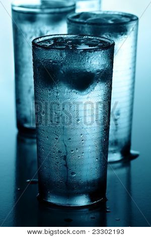 Glasses of cold water with ice cubes reflected on wet background