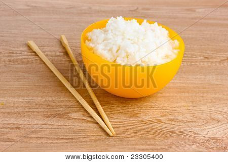 Yellow bowl of cooked rice and chopsticks on wooden table