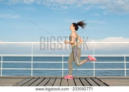 poster of Happy Latin Fit Girl Running Alone On Bridge. Student In Tracksuit Keeping Fit And Enjoying Availabl