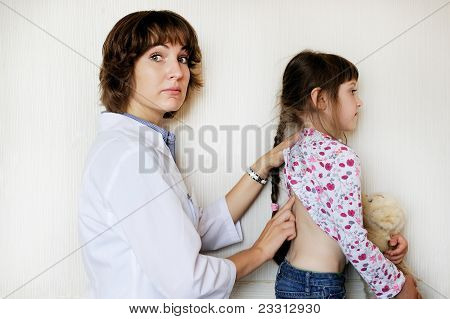 Young female doctor examining a little child girl