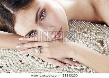 Beauty with diamond ring on pearls background