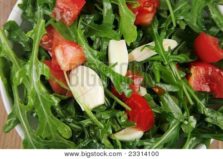healthy food : salad with raw tomato , garlic , and green staff in white bowl over wood served with cutlery
