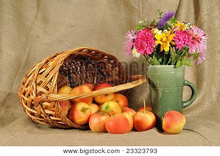 The autumn flowers and red apples