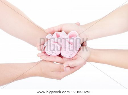 Mother's And Father's Hands Holding Pink Newborn Baby Booties. Over White.
