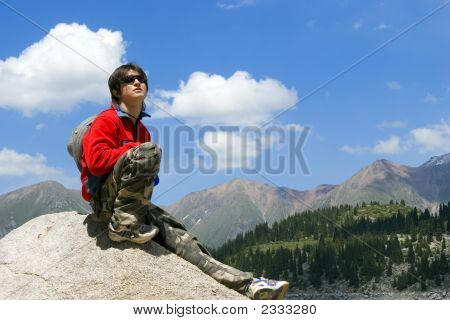 Teenager Boy In Red Sport Pullover In Mountain Hike And Blue Sky