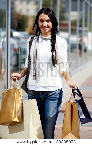 Image of happy female with paperbags walking down street