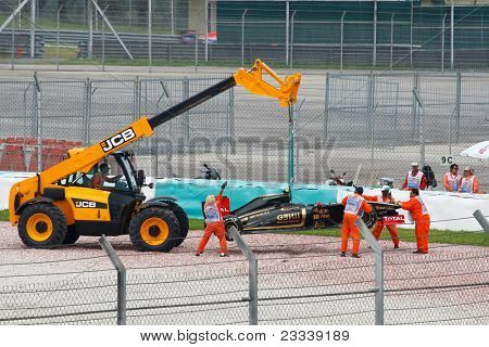 SEPANG, MALAYSIA - APRIL 8: Track officials lifting up Vitaly Petrov's car after he skidded out of the tracks during practice at the Petronas Malaysian F1 Grand Prix on April 8, 2011 in Sepang, Malaysia.
