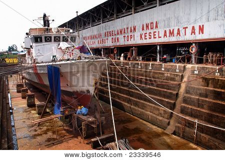 KUCHING, BORNEO ISLAND - MAY 13: Shipyard workers repair a ship in the dry dock beside the Sarawak River, May 13, 2011 in Kuching, Borneo Island. Boats and ships are important forms of transport here.