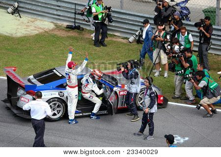 SEPANG - JUNE 19: Weider Honda Racing team drivers Takashi Kogure and Loic Duval celebrate their win of the GT500 race at the Japan SUPER GT Round 3 race on June 19, 2011 in Sepang, Malaysia.