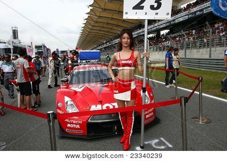 SEPANG, MALAYSIA - JUNE 19: NISMO's race queen poses in front of the team's Nissan GT-R R35 car before the start of the Japan SUPER GT Round 3 race on June 19, 2011 in Sepang International Circuit, Sepang, Malaysia.