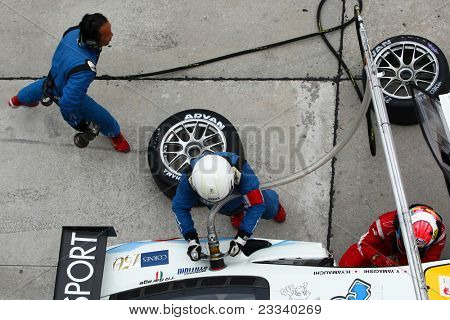 SEPANG - JUNE 19: LMP Motorsport pit crew prepares to refuel and change tires during a pit-stop of the Japan SUPER GT Round 3 race on June 19, 2011 in Sepang International Circuit, Malaysia.