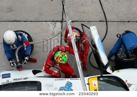 SEPANG - JUNE 19: LMP Motorsport team executes a drivers change during a pit-stop of the Japan SUPER GT Round 3 on June 19, 2011 in Sepang International Circuit, Malaysia.