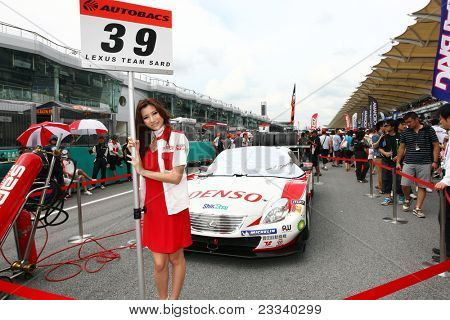 SEPANG - JUNE 19: Lexus Team Sard's race queen carries the team's placard at the start of the Japan SUPER GT Round 3 race in Sepang International Circuit on June 19, 2011 in Sepang, Malaysia.