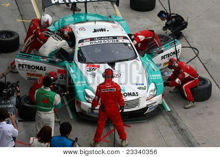 SEPANG - JUNE 19: Lexus Team Petronas Tom's pit crew prepares to refuel and change tires during a pit-stop of the Japan SUPER GT Round 3 race on June 19, 2011 in Sepang International Circuit, Malaysia