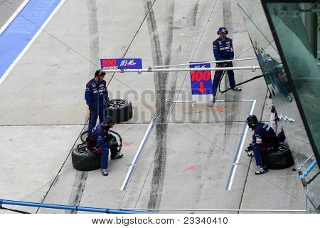 SEPANG - JUNE 19: Team Kunimitsu's pit-crew prepares for car to refuel, driver and tire change during the Japan SUPER GT Round 3 race on June 19, 2011 in Sepang International Circuit, Malaysia.
