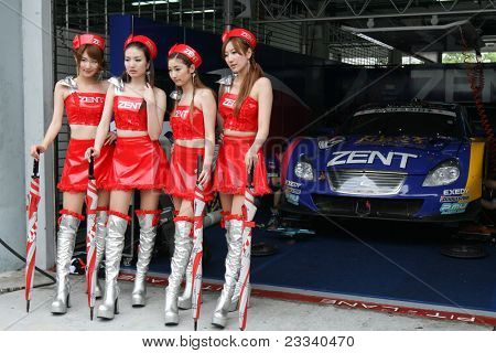SEPANG - JUNE 19: Race queens from the team of 'Lexus Team Zent Cerumo' pose with the team car at the Sepang International Circuit at the Japan SUPER GT Round 3  on June 19, 2011 in Sepang, Malaysia.