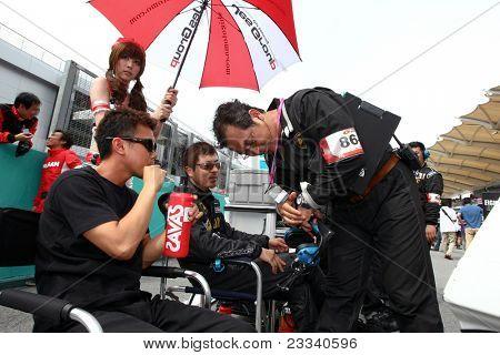 SEPANG, Malásia - 19 de junho: Yuya Sakamoto (L) e Takayuki Aoki (R) discutem com o engenheiro de corrida (stan