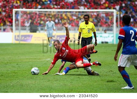 BUKIT JALIL - JULY 16: Liverpool's Joe Cole (red) falls from a tackle by Malaysia's Amar Rohidan in this game played at the National Stadium on July 16, 2011, Bukit Jalil, Malaysia. Liverpool won 6-3.