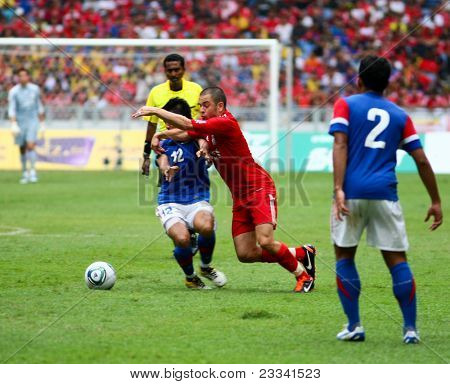 BUKIT JALIL, MALAYSIA - JULY 16 : Liverpool's Joe Cole (red) takes on Malaysia's Amar Rohidan in this game played at the National Stadium on July 16, 2011, Bukit Jalil, Malaysia. Liverpool won 6-3.