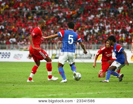 BUKIT JALIL, MALAYSIA - JULY 16: Malaysia's M. Rizal (5) intercepts a pass by Liverpool's David Ngog (red) in this game played at the National Stadium on July 16, 2011, Bukit Jalil, Malaysia.