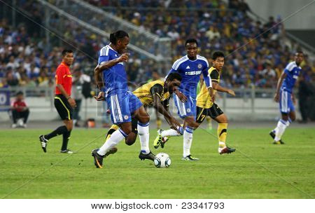 BUKIT JALIL, MALAYSIA - JULY 21: Chelsea's Didier Drogba (front, in blue) kicks the ball in a game against Malaysia at the National Stadium on July 21, 2011 in Bukit Jalil, Malaysia. Chelsea won 1-0.