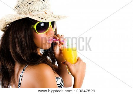 Beautiful young brunette woman in cowboy hat and sunglasses enjoying a cocktail with puckered lips - isolated on white