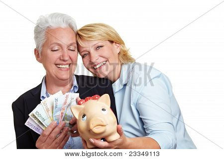 Two Women With Money And Piggy Bank