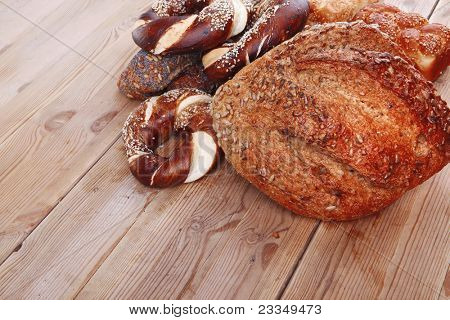 hot rural french round rye bread and baguette topped with sunflower seeds and sweet bagels on wooden tables