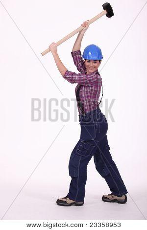 Woman raising sledge-hammer in the air
