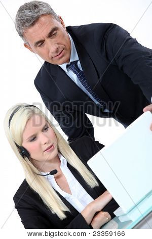Boss looking at a laptop with an employee
