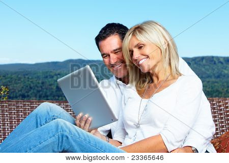 Happy smiling couple with tablet computer. People outdoors.