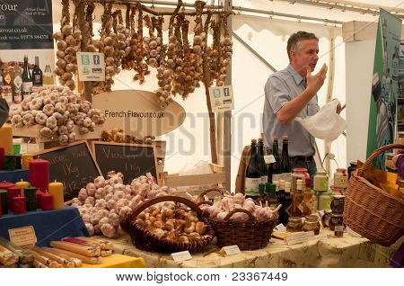 LUDLOW, UK-SEPTEMBER 11: Ludlow Food Festival, a stall holder selling his wares of garlic and cider in the main marquee in the grounds of Ludlow castle on September 11, 2011