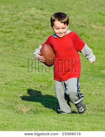 Young boy or kid running with football