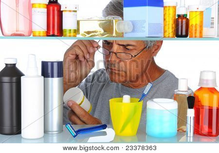 Unshaven Middle aged man reading a prescription label in front of his bathroom Medicine Cabinet. Horizontal format isolated on white.