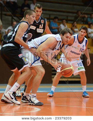 KAPOSVAR, HUNGARY - SEPTEMBER 8: Bence Biro (in white C) in action at a friendly basketball game between Kaposvar (white) and Pecsi VSK (black) September 8, 2011 in Kaposvar, Hungary.