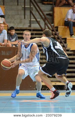 KAPOSVAR, HUNGARY - SEPTEMBER 8: Nik Raivio (in white) in action at a friendly basketball game between Kaposvar (white) and Pecsi VSK (black) September 8, 2011 in Kaposvar, Hungary.