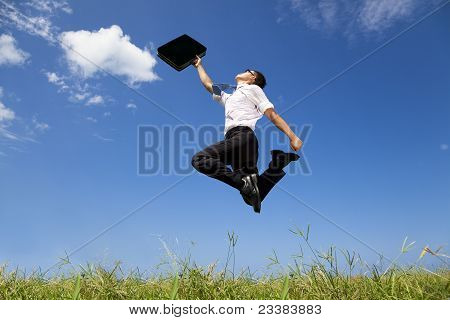 happy and successful businessman jumping on the field