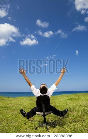 relaxed businessman sitting on the chair in green field