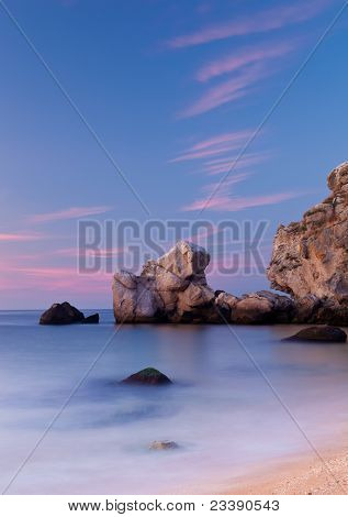 Beautiful Sunset At The Sea With Still Water And Rocks