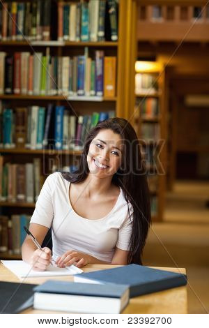 Portrait Of A Smiling Student Writing A Paper