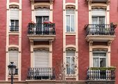 Several Windows Of Old Apartment Residential Building Of The Early Twentieth Century Red Colorful Fa poster